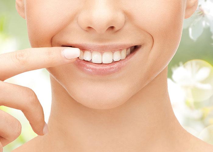 自分の歯を指でなぞる女性